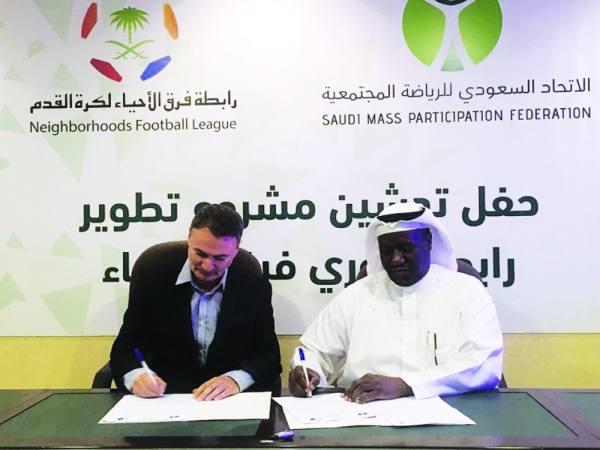 حماد الحربي رئيس الرابطة والمستشار ريتشي أثناء التوقيع