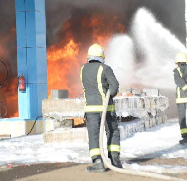أحد رجال مدني تبوك يحاول إخماد حريق في محطة وقود