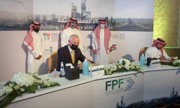 ديفيد واتكنز وآل سويد خلال توقيع الاتفاقية