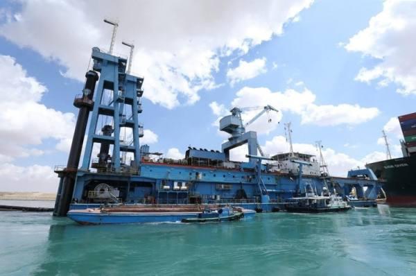 قاطرات وجرافات لتحرير السفينة العالقة بقناة السويس