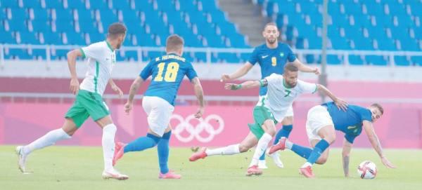 الفرج يحاول استخلاص الكرة من لاعب البرازيل